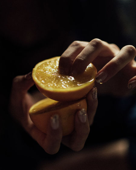 Cropped hands of woman holding halved lemon