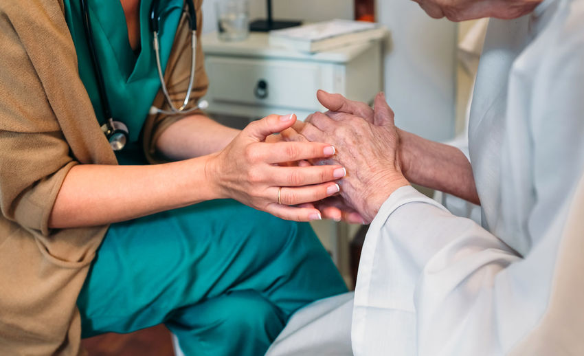 Female doctor giving encouragement to elderly patient by holding her hands Bed Care Doctor  Holding Hands Horizontal Hospital Loving Nursing Woman Aged Clinic Elderly Encouragement Examining Health Care Healthcare And Medicine Home Assistance Home Assistant Illness Medical Nursing Home Patient Senior Treatment Two People