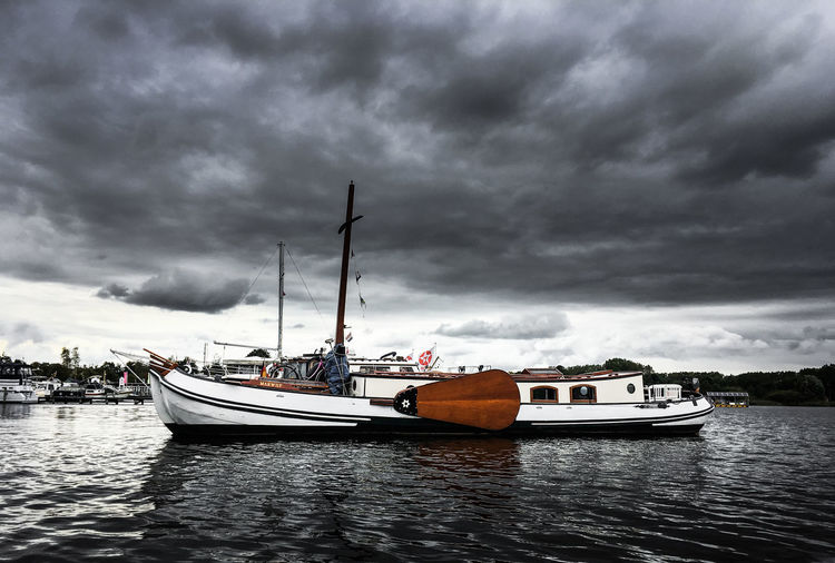 Boats sailing in calm sea against cloudy sky