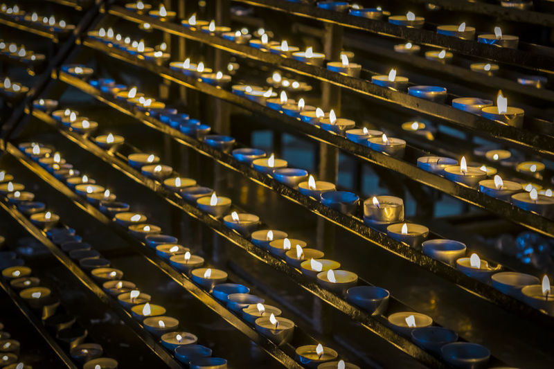 Candles glow in dark. Christian religion, prayer concept. Burning candles, candlelight in catholic church. Candles Catholic Christian Church Dark Flame Gold Holiday Hope Lights Meditation Tranquil Black Blue Burn Candelight Decoration Fire Glow Glowing Religion Religious  Spiritual Symbol Wax