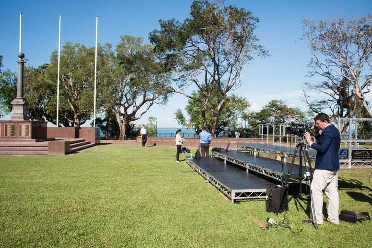 Darwin,NT,Australia-April 10,2018: Press setting up equipment on Day of Prince Charles wreath ceremony at Bicentennial Park in Darwin, Australia Australia Darwin Event Journalist Memorial Press War Memorial Bicentennial Park Cenotaph Memorial Event Men News Occupation Outdoors Plant Professional Real People Royal Standing Television Camera Television Industry Tree Tripod Video Camera Waterfront