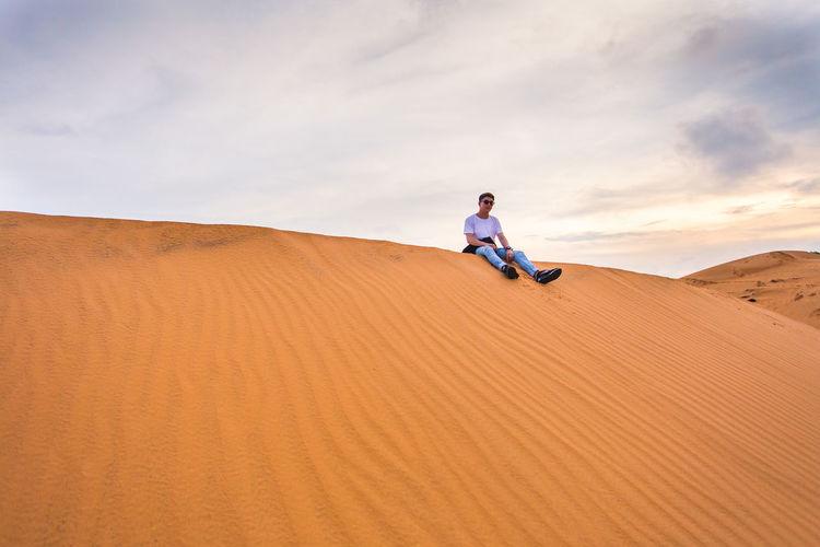 Man on sand dune at desert against sky