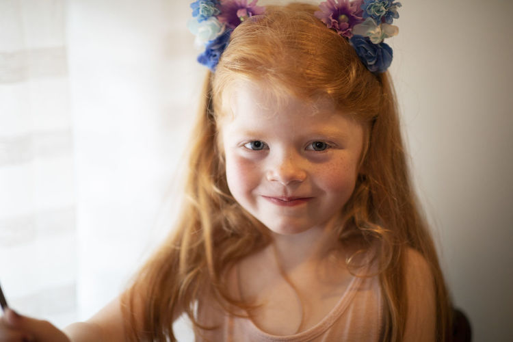 A five-year-old red head blue eyed girl sits for a natural light portrait in her home with bows in her hair. Portrait Childhood Child Offspring Headshot Hair Looking At Camera One Person Innocence Females Women Hairstyle Indoors  Smiling Girls Long Hair Cute Happiness Redhead Human Hair Small Red Hair Blue Eyes Happiness Five-year-old