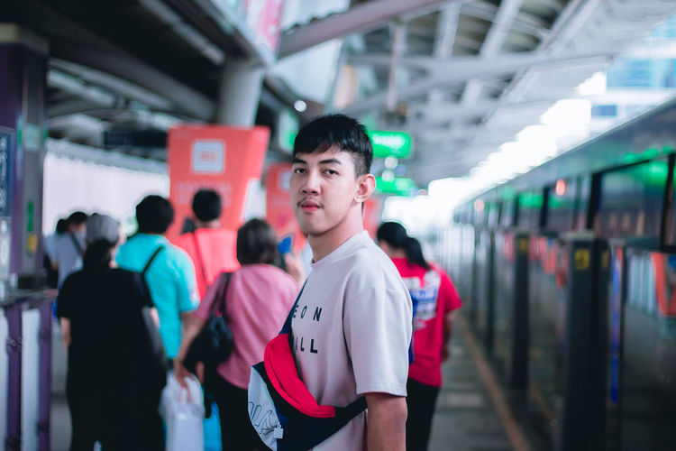 Real People Standing Lifestyles Focus On Foreground Incidental People Leisure Activity People Architecture Men Transportation Casual Clothing Indoors  Day Waist Up Women Railroad Station Looking Away