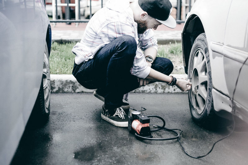 Young man inflating car tire with air pump at parking lot