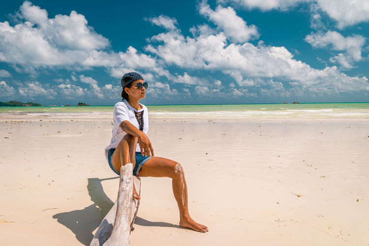 Full length of woman sitting at beach against sky