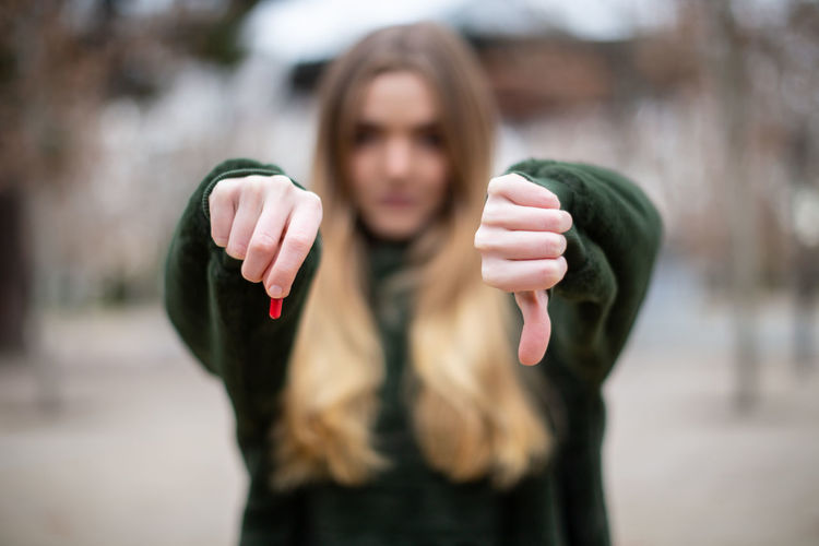 Close-up portrait of woman with pill showing thumbs down