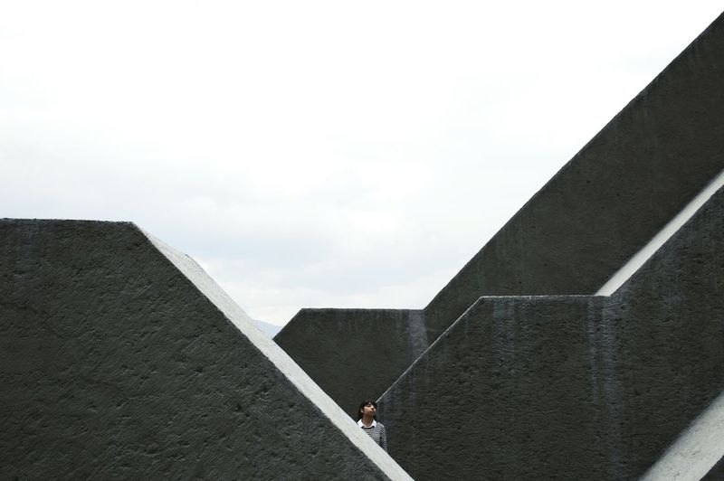 Woman Standing Amidst Concrete Structures Against Sky