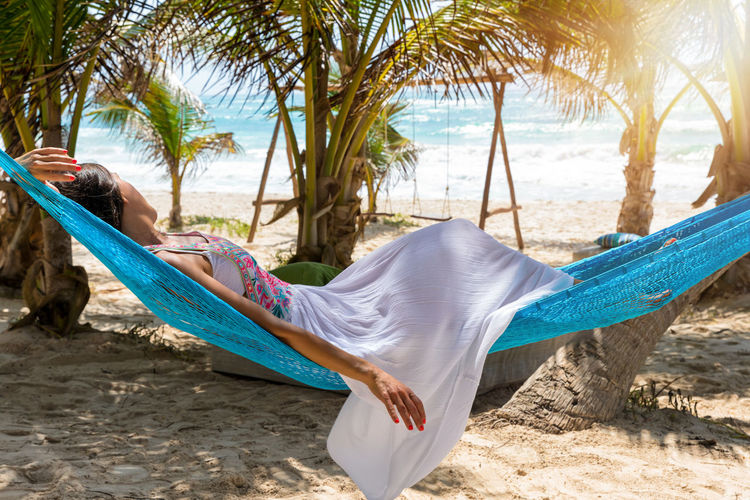 Young Woman Relaxing On Hammock At Beach