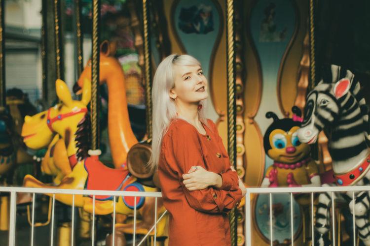 The girl standing near the carousel