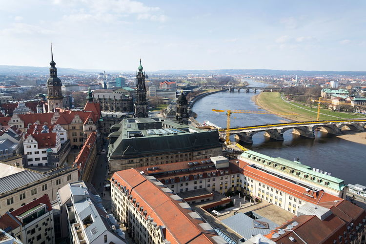 Aerial view of Dresden cathedral of the Holy Trinity with Augustus bridge over Elbe in Dresden, Germany, sunny spring day Dresden Cathedral Holy Trinity Church Royal Court Hofkirche Sanctissimae Trinitatis Bridge Augustus Repair Catholic Religion Crane Elbe River Construction Site Aerial View Real People Restoration Arch Stone History Tourist Famous Landmark Place Germany City Centre Saxony Monument Statue World Man Building Architecture Museum Unesco Gallery Copy Space Horizontal