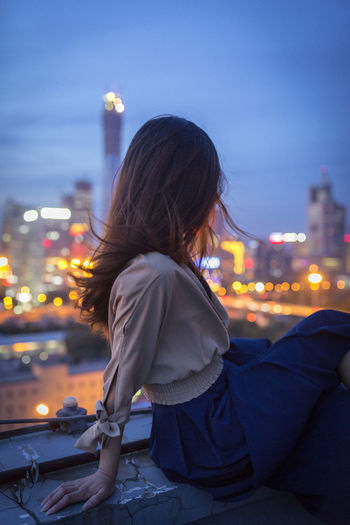 Rear view of woman in illuminated city against sky at night