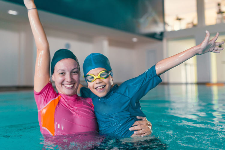 Portrait of cheerful with teacher in swimming pool
