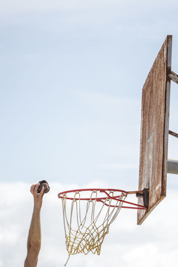 Cropped hand throwing stone over basketball hoop against sky