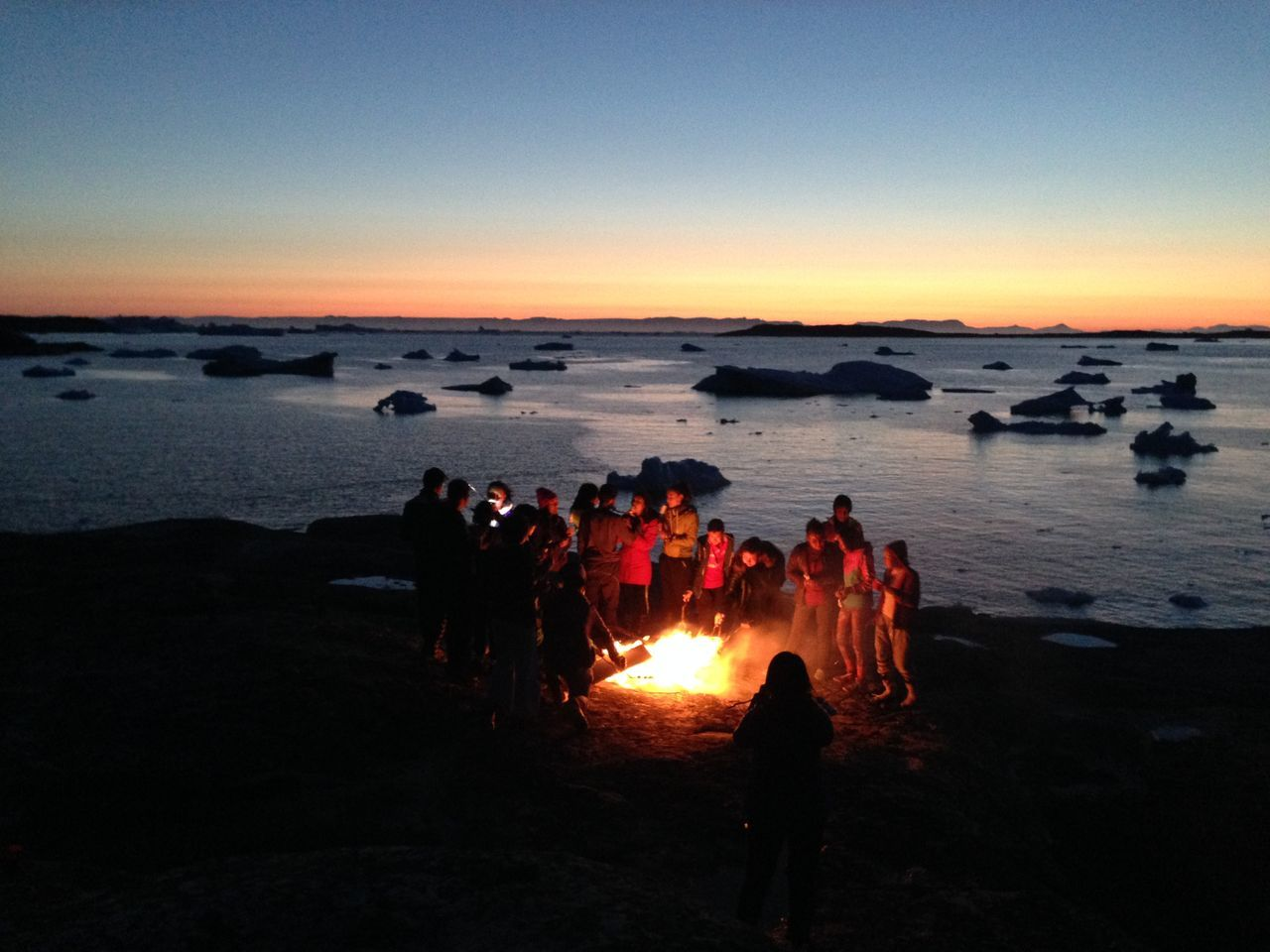 View of people surrounding bonfire on beach