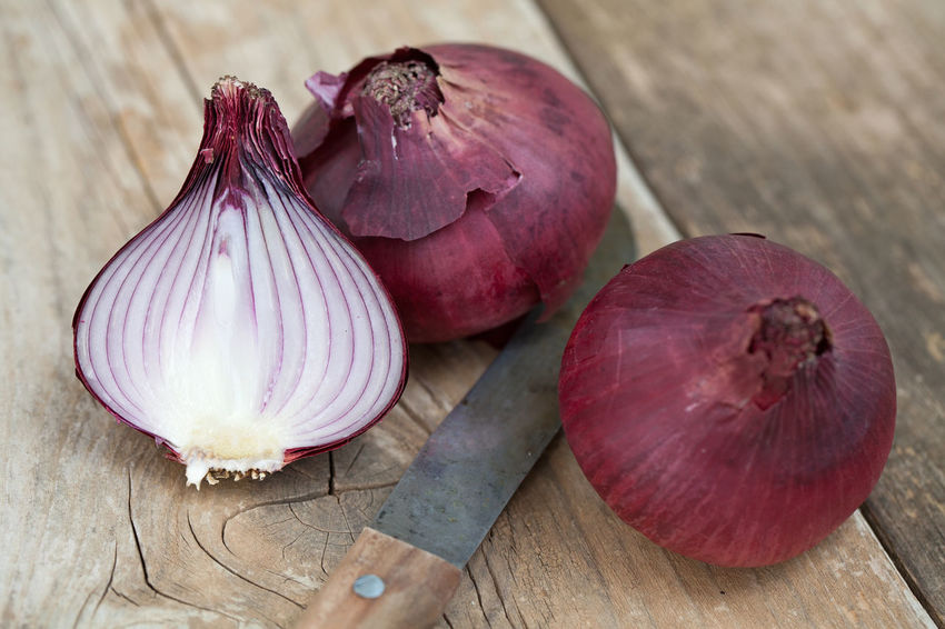 One whole and a half red onions on a cutting board Bulb Chopped Close-up Cross Section Cutting Board Food Food And Drink Freshness Half Harvest Healthy Eating High Angle View Indoors  Ingredient Kitchen Knife No People Onion Purple Raw Food Red Color SLICE Still Life Table Vegetable Wood - Material