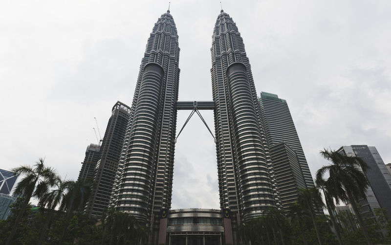 KUALA LUMPUR, MALAYSIA - AUGUST 31, 2016: The Petronas Towers were designed by Argentine architect Cesar Pelli. They chose a distinctive postmodern style to create a 21st-century icon for Kuala Lumpur. Architecture Building Exterior Built Structure City Day Landmark, Kuala, Lumpur, Malaysia, Skyline, Cityscape, Klcc, Business, Architecture, Scene, Skyscraper, Travel, Downtown, Twin, Urban, Shopping, Tower, City, Capital, Asia, Modern, Building, Office, Petronas, Park, Famous, View, Tall, Center, Morning, Tal Low Angle View Modern No People Outdoors Sky Skyscraper Tall Tall - High Travel Destinations Tree