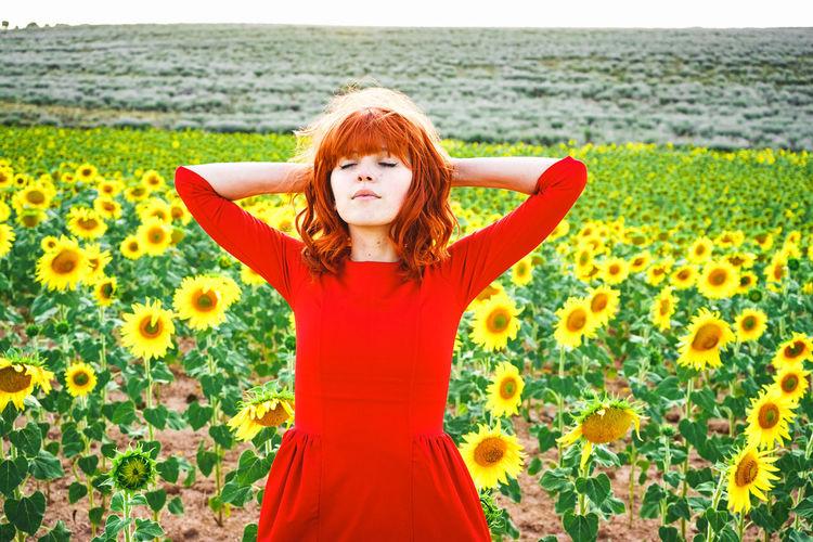 Portrait of beautiful woman standing on field