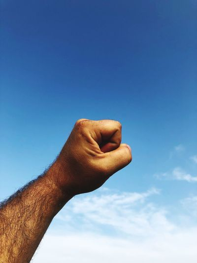 Cropped hand of man gesturing fist against blue sky