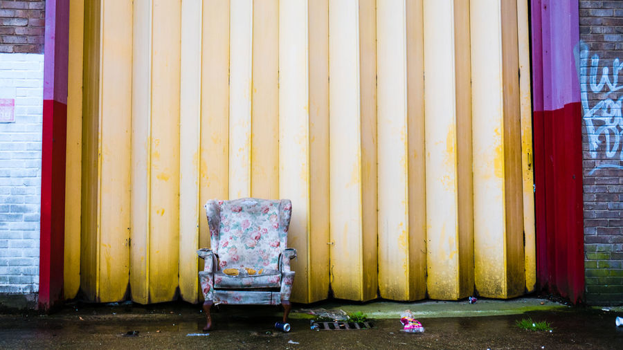 Abandoned armchair against wall