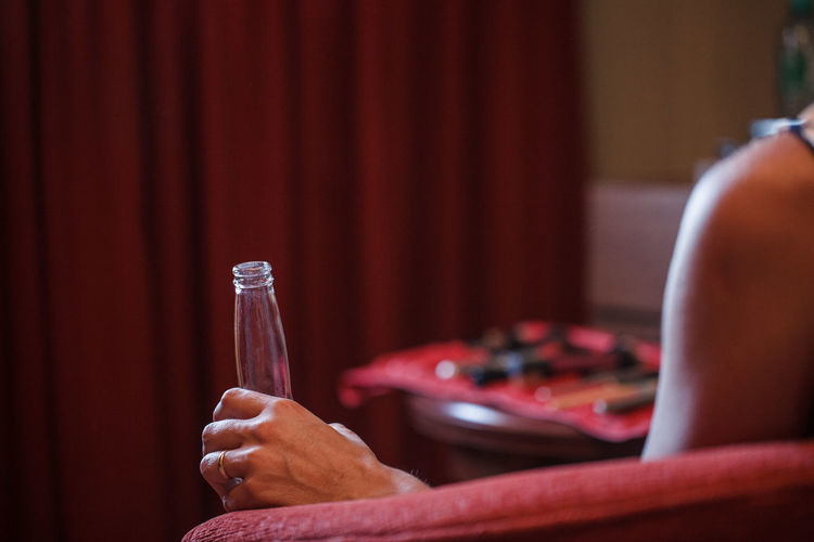 Cropped image of woman with bottle sitting on chair