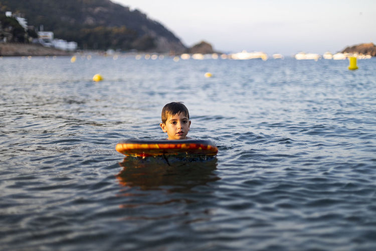 Boy looking away while surfing on sea