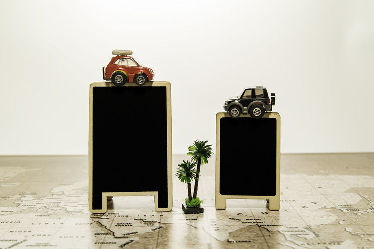 Two blank black boards with car on top on world map with palm tree Atlas Map Palm Tree Advertising Agency Announcements Black Board Table Blanket Car Day Indoors  No People Old-fashioned Signboard Studio Shot White Background World Map