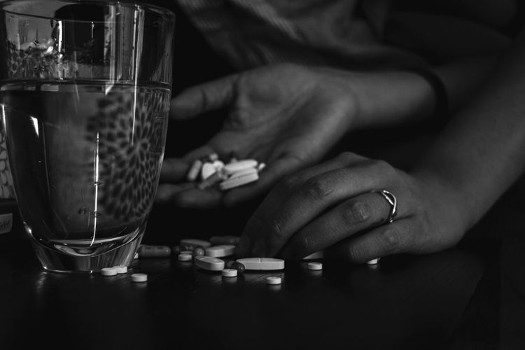 Cropped hand holding pills at home