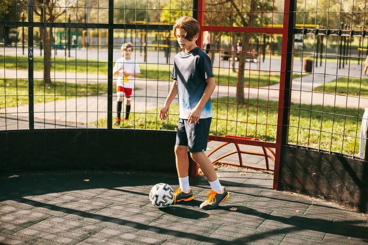 A young man in a sports uniform trains with a ball on the freestyle football court.