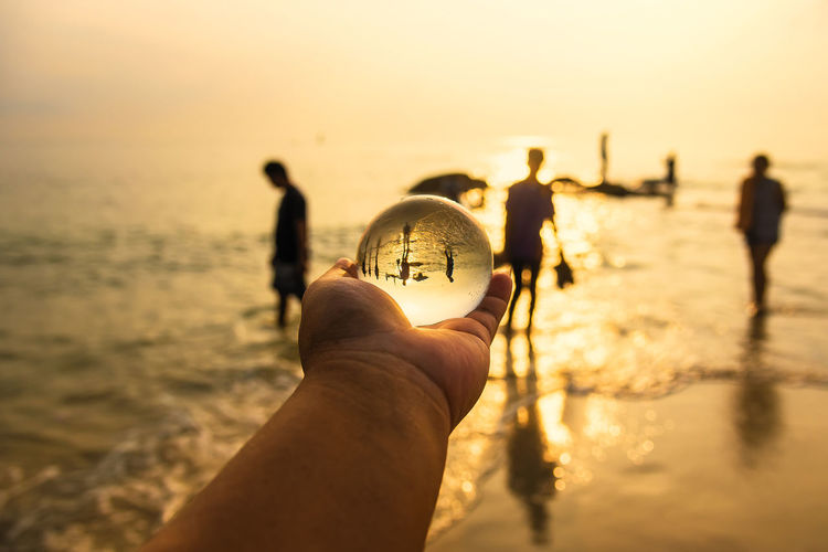 Cropped hand of person holding crystal ball with people in background against sea and sky during sunset