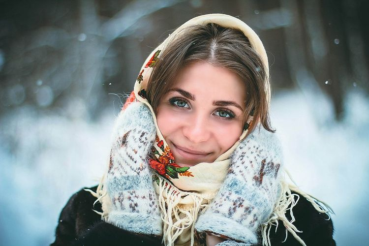 Portrait of smiling woman with scarf in snow