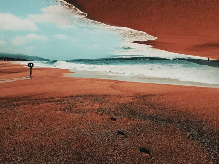 Surreal scenic view of beach by sea against sky