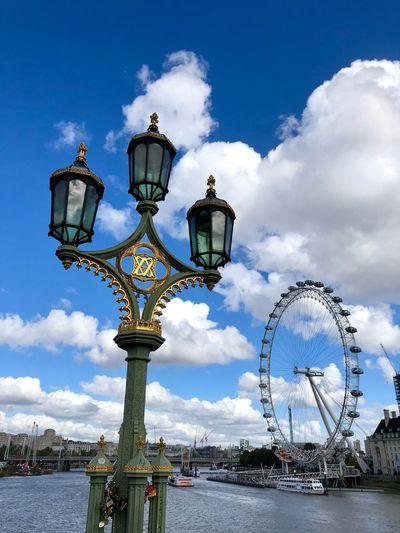 Street light against millennium wheel by thames river