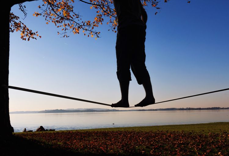 Slacklining Low Section Leisure Activity Real People Clear Sky Silhouette Outdoors One Person Lifestyles Nature Sky Sunset Human Leg Men Day Blue Standing Water Beauty In Nature Tree People Slackline Tightrope Sport Work Life Balance