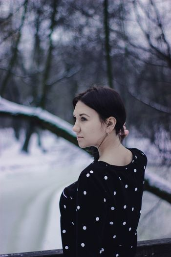 Close-up of young woman against trees