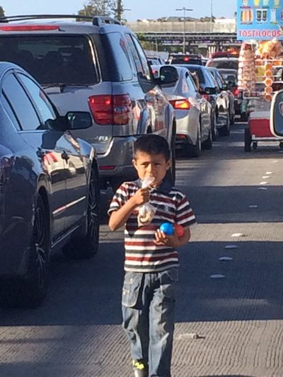 Editorial October 2, 2016. Young boy standing between cars at the US - Mexico border crossing in Otay Mesa Mode Of Transport Us Mexico Border Border Crossing Illegal Immigration Immigration Immigrants Immigrant Politics Political Election2016