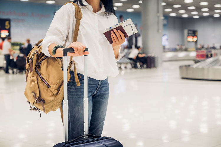 Midsection of woman standing with luggage at airport