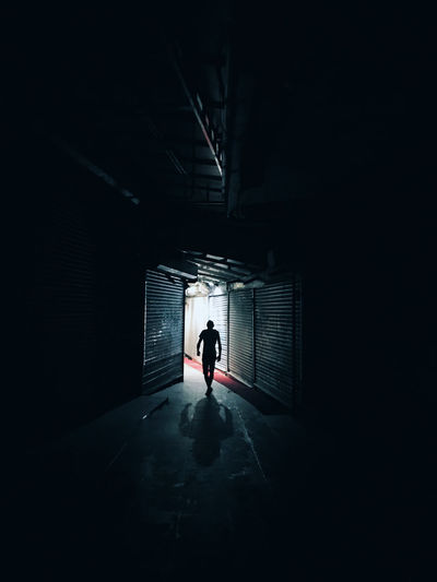 in shadow The Street Photographer - 2018 EyeEm Awards Architecture Built Structure Ceiling Dark Direction Full Length Illuminated Indoors  Lifestyles Light At The End Of The Tunnel Men One Person Public Transportation Real People Rear View Silhouette Standing Streetphotography The Way Forward Transportation Tunnel HUAWEI Photo Award: After Dark