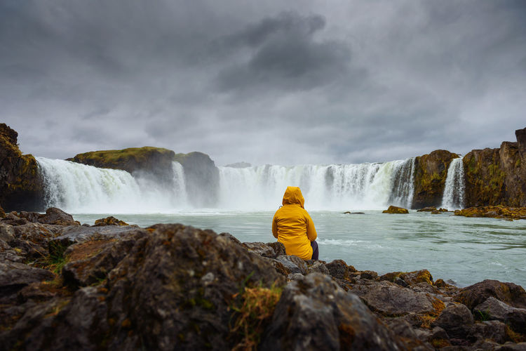 Rear view of man looking at waterfall against sky