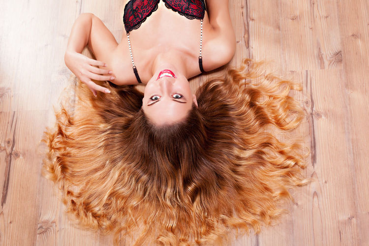 High Angle View Of Woman In Bikini Lying On Floor At Home