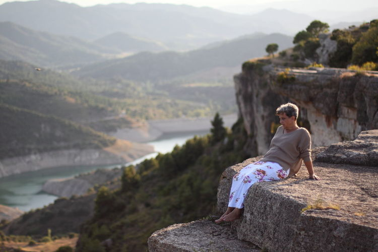 Man sitting on rock looking at mountains