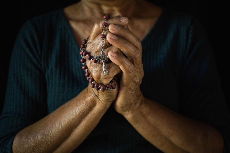 Midsection of woman praying with rosary