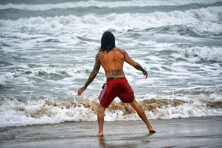 Rear view of shirtless man wading in sea