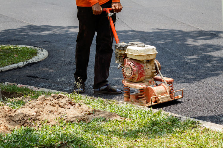 Low section of manual worker with machinery working on road