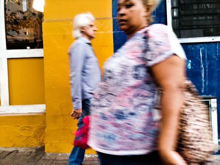 Side view of blurred motion of woman walking in city