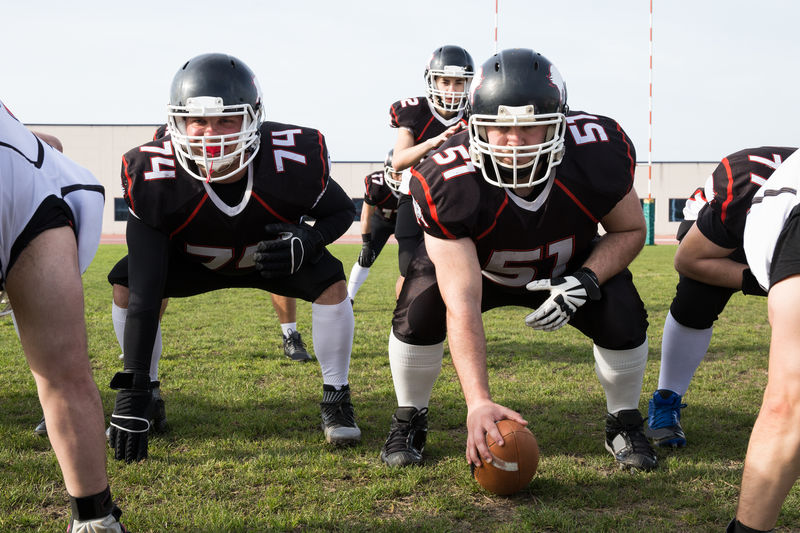 Full Length Of American Football Players With Ball Bending On Field