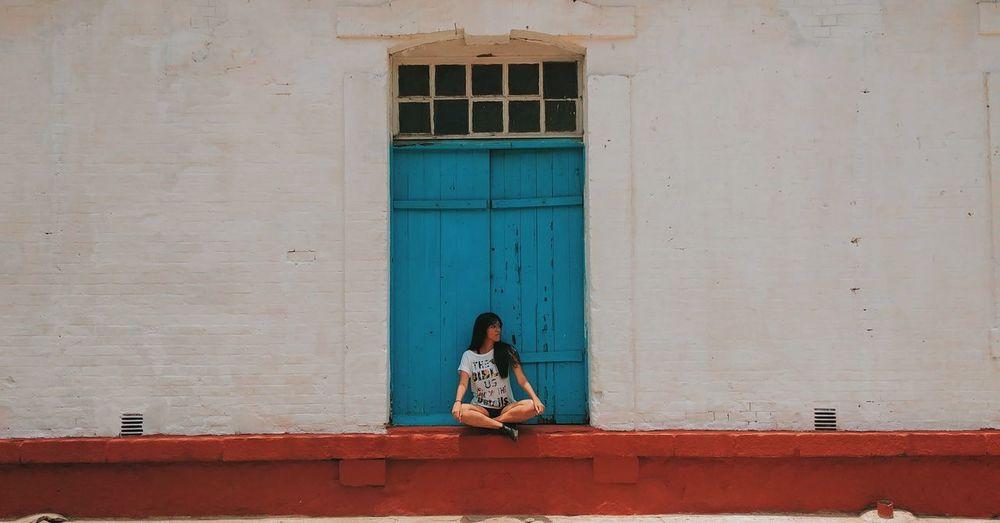 Woman sitting against window