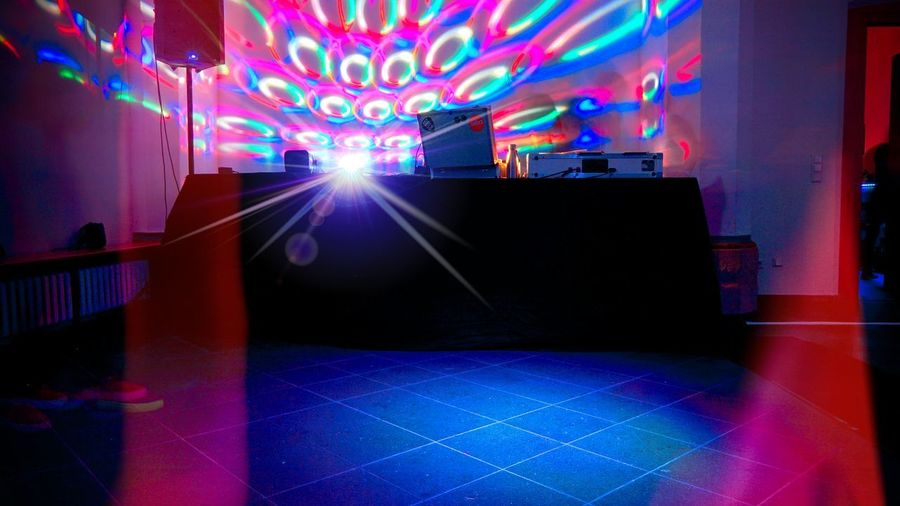 Illuminated lights on tiled floor at night