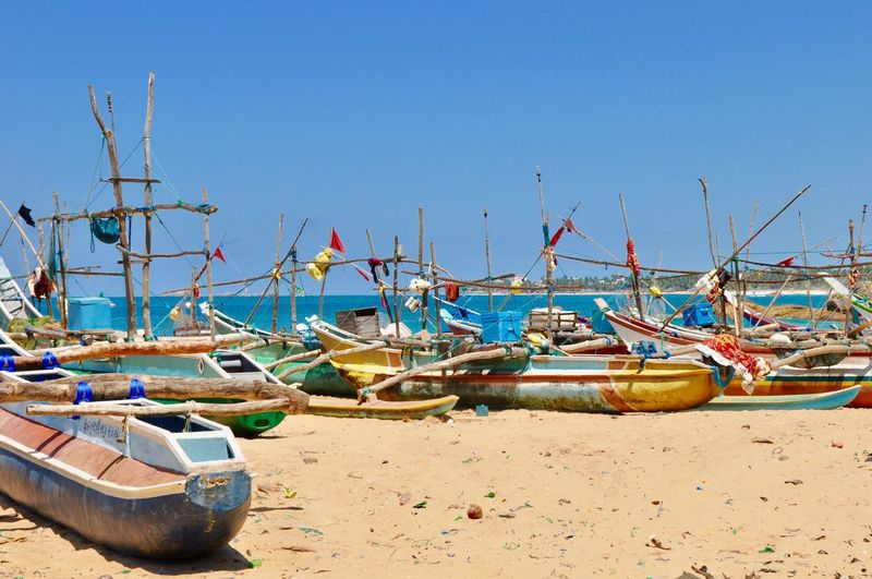 Boats moored on shore at beach against clear blue sky