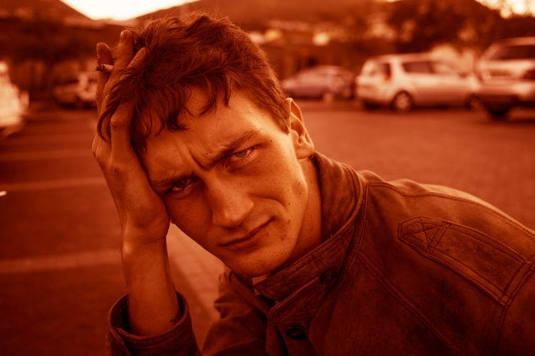 Portrait of worried man holding cigarette at parking lot